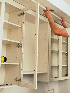 Cabinetmaker installing kitchen cabinets.